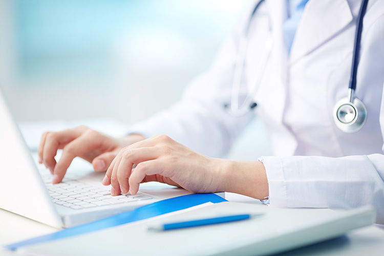 Medical person in a white coat typing on a laptop