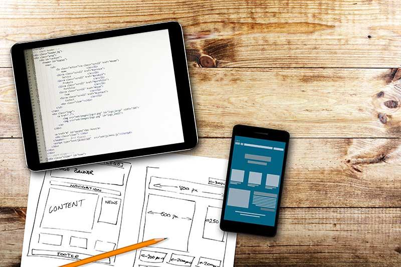Website wireframe sketch and programming code on digital tablet - NH