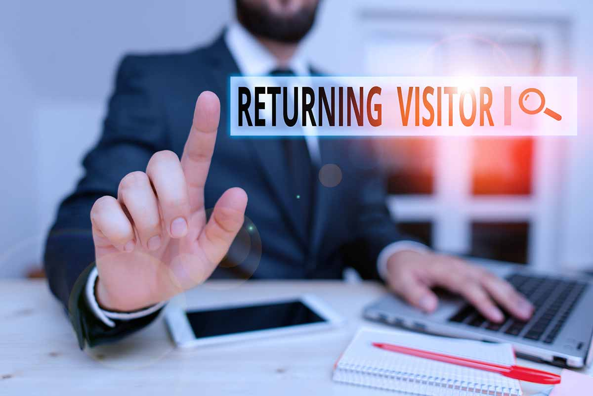 """A man reaching forward to click an illustrated graphic of a search tool bar with the words, """"Returning Visitor"""" spelled out in search field."""