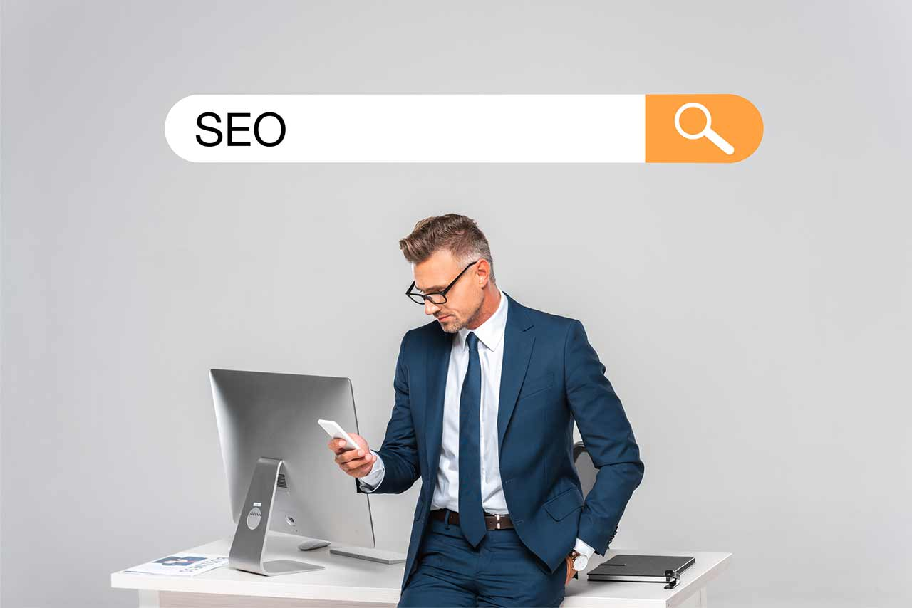 Small business owner leaning on his desk as he does a mobile search for SEO strategy.